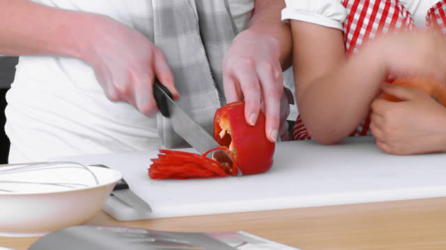 CU Mother with son (8-9) chopping red bell pepper / Cape Town, South Africa