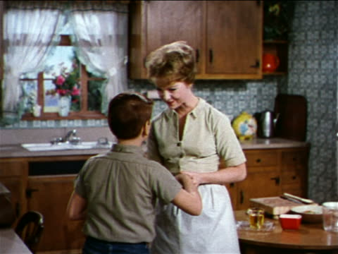1962 mother with son in kitchen taking off apron / industrial - apron stock videos and b-roll footage