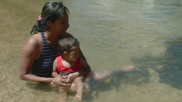 ms mother with son (18-23 months) in river / yelapa, jalisco, mexico - 18 23 months stock-videos und b-roll-filmmaterial