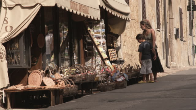 ws mother with son looking at baskets for sale outside store / tuscany, italy - korb stock-videos und b-roll-filmmaterial