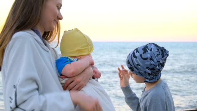 stockvideo's en b-roll-footage met moeder met de zonen aan kust - 6 11 maanden