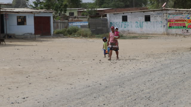 A mother with two children walking on a simple village