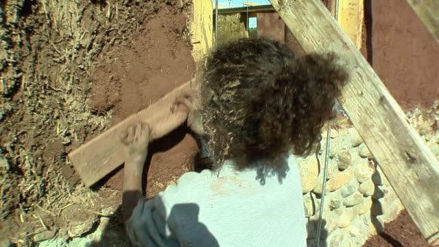 cu zo ms mother with two daughters (4-5, 6-7) applying adobe mud mixture to wall of straw house under construction, grass lake, michigan, usa - straw stock videos & royalty-free footage