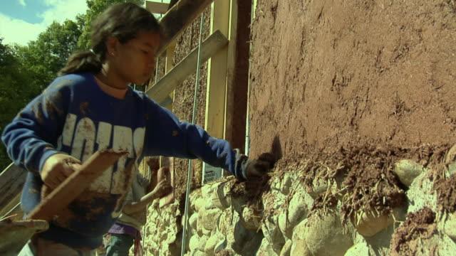 cu mother with two daughters (4-5, 6-7) applying adobe mud mixture to wall of straw house under construction, grass lake, michigan, usa - adobe bildbanksvideor och videomaterial från bakom kulisserna