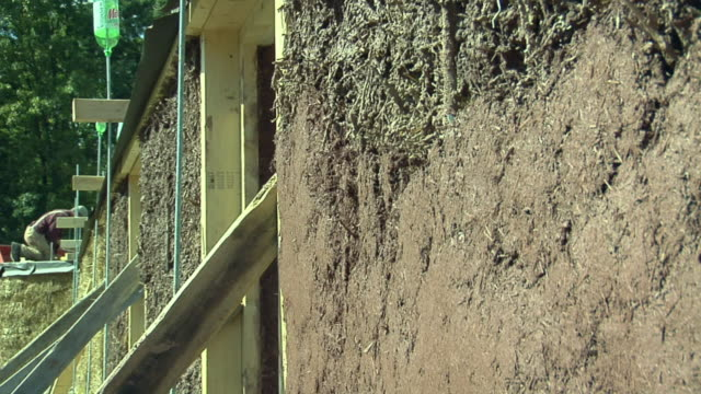 cu mother with two daughters (4-5, 6-7) applying adobe mud mixture to wall of straw house under construction, grass lake, michigan, usa - straw stock videos & royalty-free footage