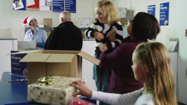 ms tu mother with two daughters (4-11) packing christmas gifts into cardboard box at post office / orem, utah, usa - postamt stock-videos und b-roll-filmmaterial