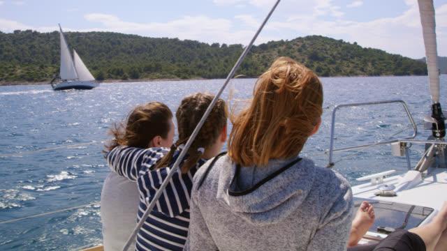 WS-Mutter mit zwei Töchtern sitzen auf einem Deck Segeln Segelboot