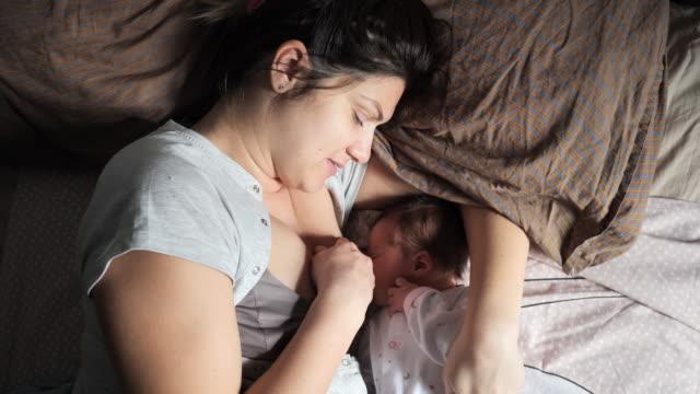 stockvideo's en b-roll-footage met de moeder met zichtbaar postpartum lichaam merkt het geven van borstvoeding - buik