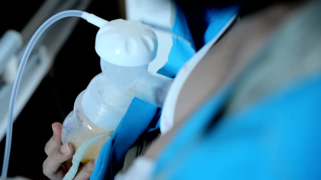 mother woman using a breast pump breast milk from the breast. - breastfeeding stock videos and b-roll footage