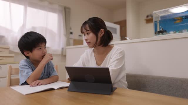 vidéos et rushes de mère qui travaille et aide son fils à faire ses devoirs à la maison - un jour comme les autres images en série