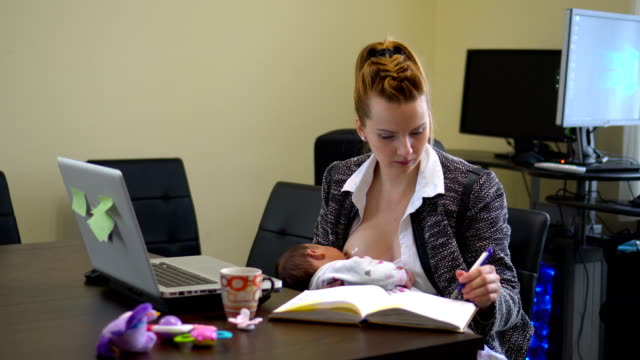 Mother working and breastfeed her baby in office