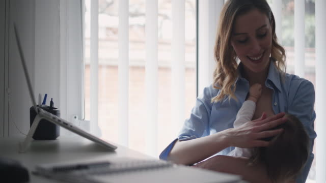 4K: Mother working and breastfeed her baby in office.