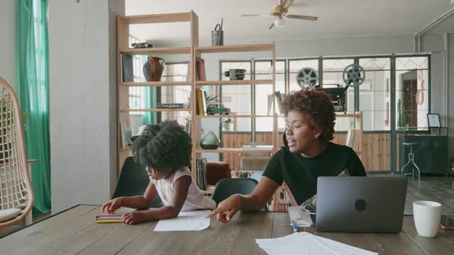 自宅で働く母親と娘が彼女の側で絵を描く - アフリカ系カリブ人点の映像素材/bロール