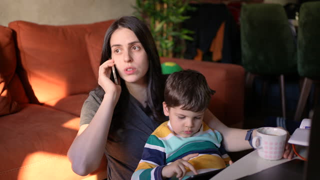 vidéos et rushes de mère travaillant à la maison tandis que son fils s'assied à ses genoux jouant aux jeux vidéo - son