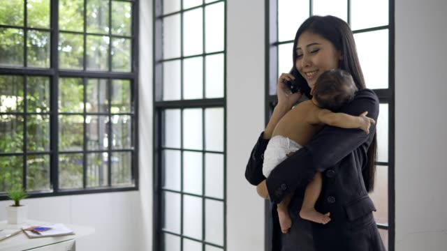 mother working at home with asian baby boy.embracing and kiss boy . - working mother stock videos & royalty-free footage