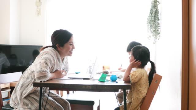 vídeos de stock, filmes e b-roll de mãe trabalhando em casa com filhos - vida simples