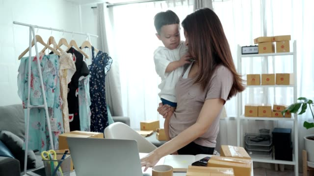 mother working from home and holding her baby - indoors stock videos & royalty-free footage