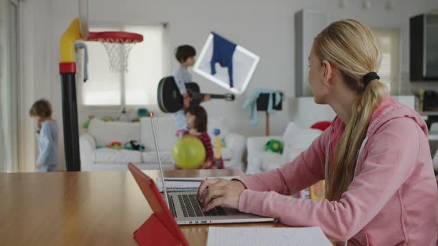 mother working from home while her kids playing at the background - trött bildbanksvideor och videomaterial från bakom kulisserna