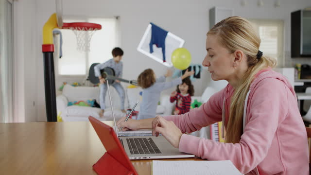 mother working from home while her kids playing at the background - 40 44 jahre stock-videos und b-roll-filmmaterial