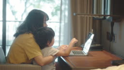 Mother working from home with her son at home.