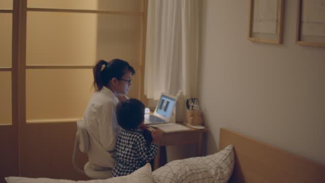 vidéos et rushes de mère travaillant de la maison avec son fils la nuit. - son
