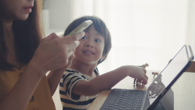 mother working from home with her son - interactivity stock videos & royalty-free footage