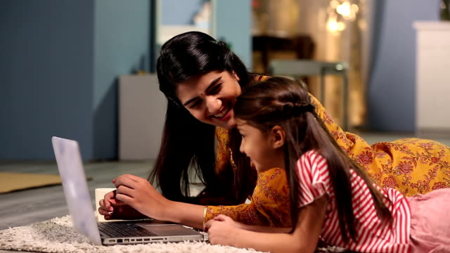 mother working on laptop with her daughter, delhi, india - ラグ点の映像素材/bロール