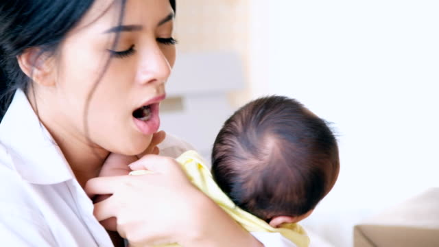 Mother working small business on laptop with baby at home.Startup small business owner working at home.Online selling, e-commerce, shipping,work at home concept
