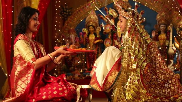 ms mother worshiping her daughter during durga puja festival / new delhi, delhi, india - meno di 10 secondi video stock e b–roll