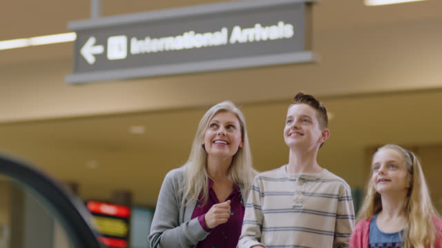 "mother, young daughter and son wave and hold ""welcome home"" sign at airport arrivals. - homecoming stock videos & royalty-free footage"