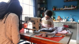 Mother-in-law teaching daughter-in-law how to use sewing machine