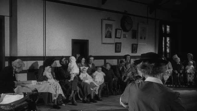 1952 montage mothers and children in crowded clinic waiting room, district nurse at desk with patient records, various children being weighed, and toddler eating a snack / wadhurst, england, united kingdom - wadhurst video stock e b–roll