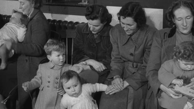 1952 montage mothers and children in waiting room at clinic in crowded waiting room / wadhurst, england, united kingdom - wadhurst stock videos & royalty-free footage