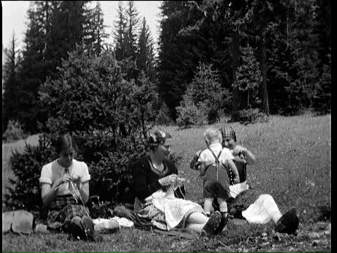 stockvideo's en b-roll-footage met 1937 b/w montage mothers and children resting on mountain meadow / bavaria, germany - 1937