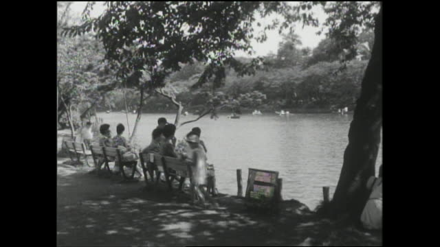 Mothers and children sit on park benches and watch boaters on Inokashira Pond.