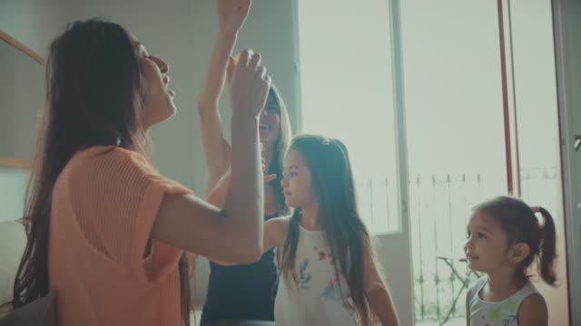 Madres e hijas teniendo diversión que sopla burbujas