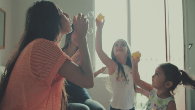 mothers and daughters having fun blowing bubbles - donne di età media video stock e b–roll