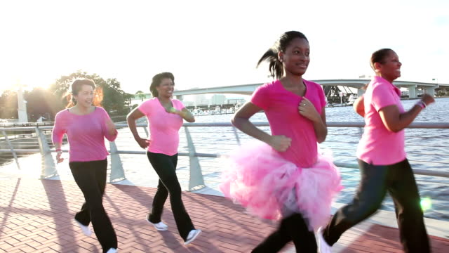 mothers and daughters running for breast cancer charity - charity benefit stock videos & royalty-free footage