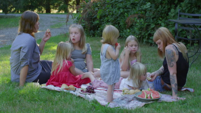 MS Mothers and daughters sitting on blanket outdoors having a picnic