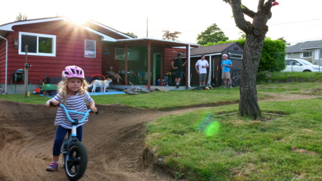 vidéos et rushes de ms mothers and fathers watching kids riding bmx bikes on backyard dirt track on summer evening - 45 49 ans