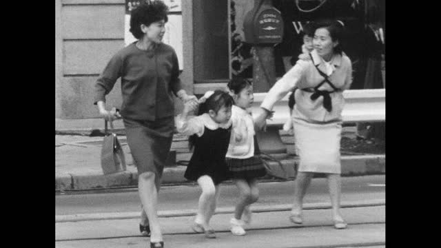 vidéos et rushes de mothers and small children run across road in tokyo; 1964 - tante