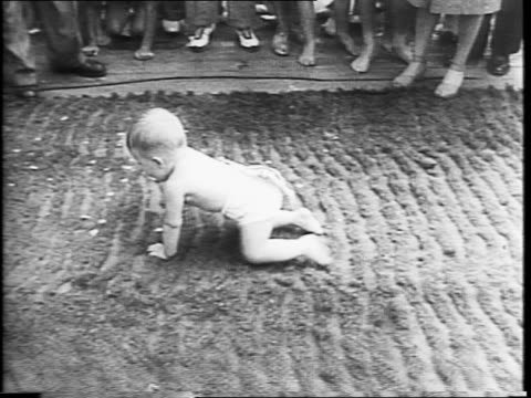 mothers carrying babies through crowd / baby standing on head, looking between his legs / montage of babies lined up on 'training table' and being... - crawling stock videos & royalty-free footage