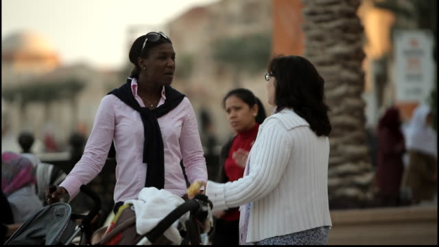mothers chatting in a park. view of two mothers, one black woman and one white woman, standing next to baby strollers talking in a park. - gulf countries stock videos & royalty-free footage