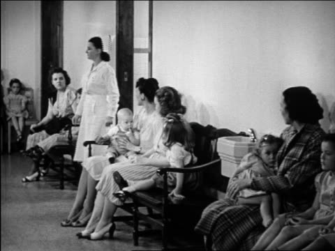 B/W 1948 mothers + children in doctor's waiting room / Michigan / medical industrial
