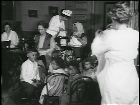 b/w 1920 pan mothers + children in large room with sewing machines / detroit, michigan / newsreel - newsreel stock videos & royalty-free footage