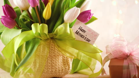 mother`s day arrangement with tulip bouquet and a gift box - mother's day stock videos & royalty-free footage
