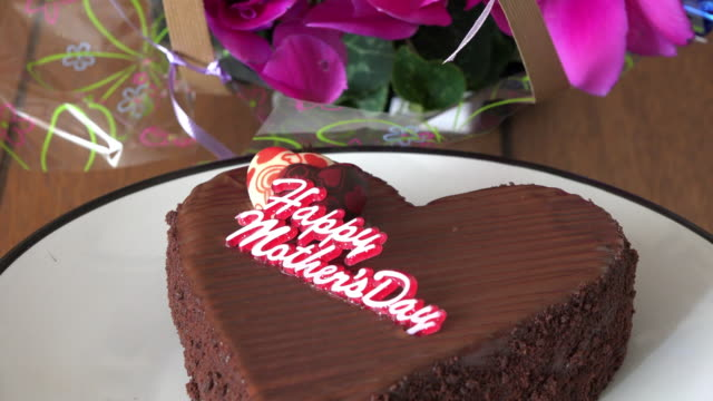 mother's day chocolate cake on a white plate over a table. there is a bouquet of flowers in the background - mother's day stock videos & royalty-free footage