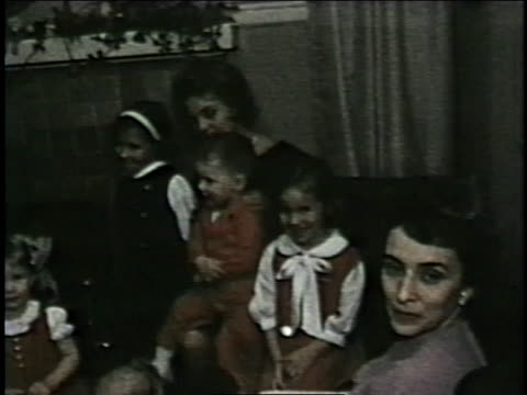 stockvideo's en b-roll-footage met mothers, fathers and children watch two little boys dance in front of the christmas tree. - 1963