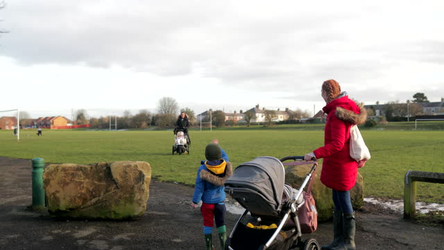 mother's going for a walk outdoors - family with two children stock videos & royalty-free footage