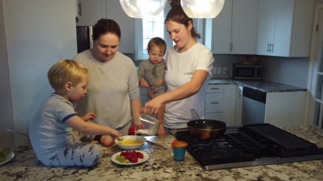 mothers multitasking in the kitchen with kids - lesbian couple with children having breakfast - multi tasking stock videos & royalty-free footage